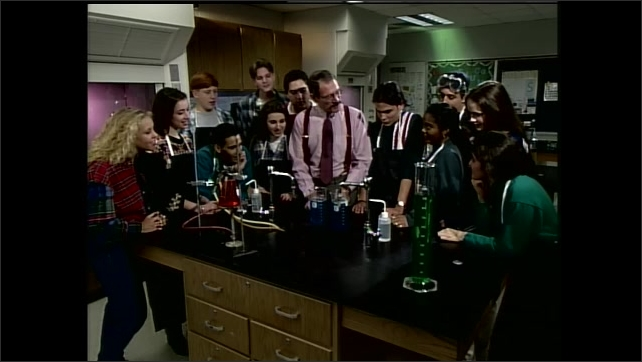1990s: Teachers speaks to class. Hand drops tablet in beaker of chemicals. Teacher and students talk and react around classroom lab table.