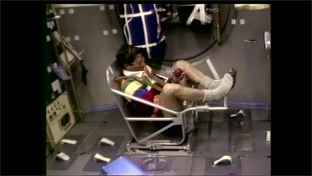 1990s: Man sits in body mass measuring device on Spacelab. Man holds up weight and speaks. Boy turns and speaks to group of students in classroom.