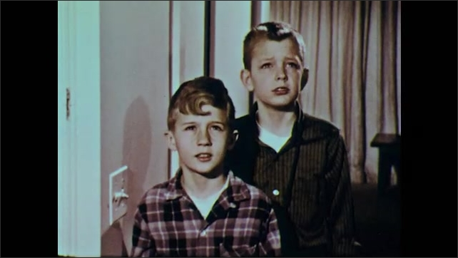 1960s: Light hanging from ceiling in house is turned on. Two boys stand looking at light, shaking heads, talking. Boys walk away.