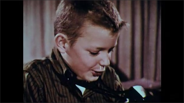 1960s: Boy in house talks then holds up camera. Fish in aquarium tank. Boy takes photo with camera. Boys in front of aquarium. Boy.