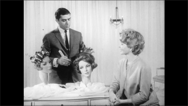 1950s: man in suit and necktie uses comb to brush hair on woman in dress, talks and touches two mannequin heads with wigs and curlers on table near curtain and chandelier.
