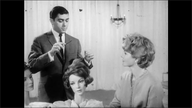 1950s: man in suit and necktie uses comb to brush hair on two mannequin heads with wigs and curlers, gestures with hands and talks to woman in dress at table near curtain and chandelier.