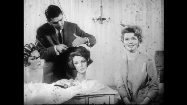 1950s: man in suit and necktie combs hair of wig on mannequin head at table as woman in dress talks and smiles near curtain and chandelier.