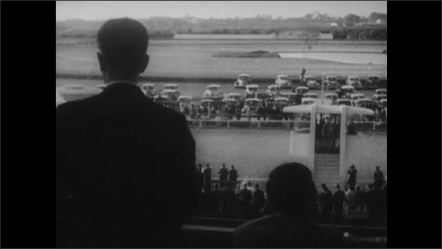1940s: SOUTH AMERICA: LIMA: PERU: men in suits watch races. Horses race around track. People watch races through glass.