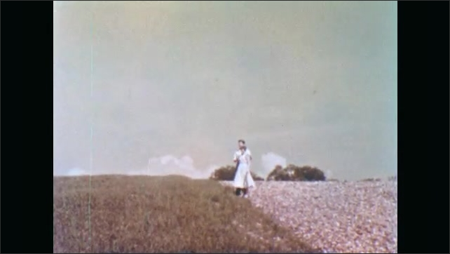 1950s: Man and woman hold hands and run in field. Man and woman stop to embrace. Man and woman hold hands and run through field.