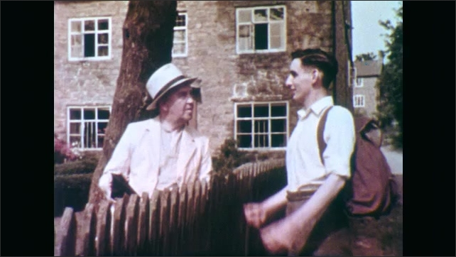 1950s: People and cows gather among houses on street. Men talk over picket fence. Man in hat nods and smiles. Men talk over picket fence. Man and girls walk along road.