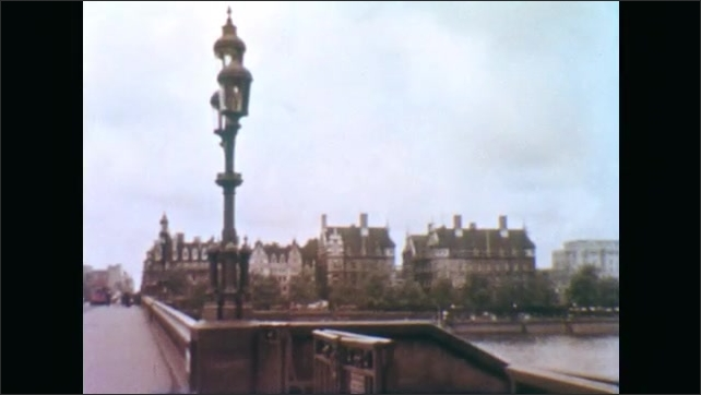 1950s: Cars cross Westminster bridge into London. Lamppost on bridge leading into city. Lamppost and Big Ben clocktower.