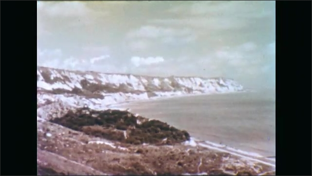 1950s: Dirt road runs through wooded landscape. Thatch roofed homes in woods. Man sits on hillside. London city. Cliffs of Dover. Couple point and run through field. Fields and hedges.
