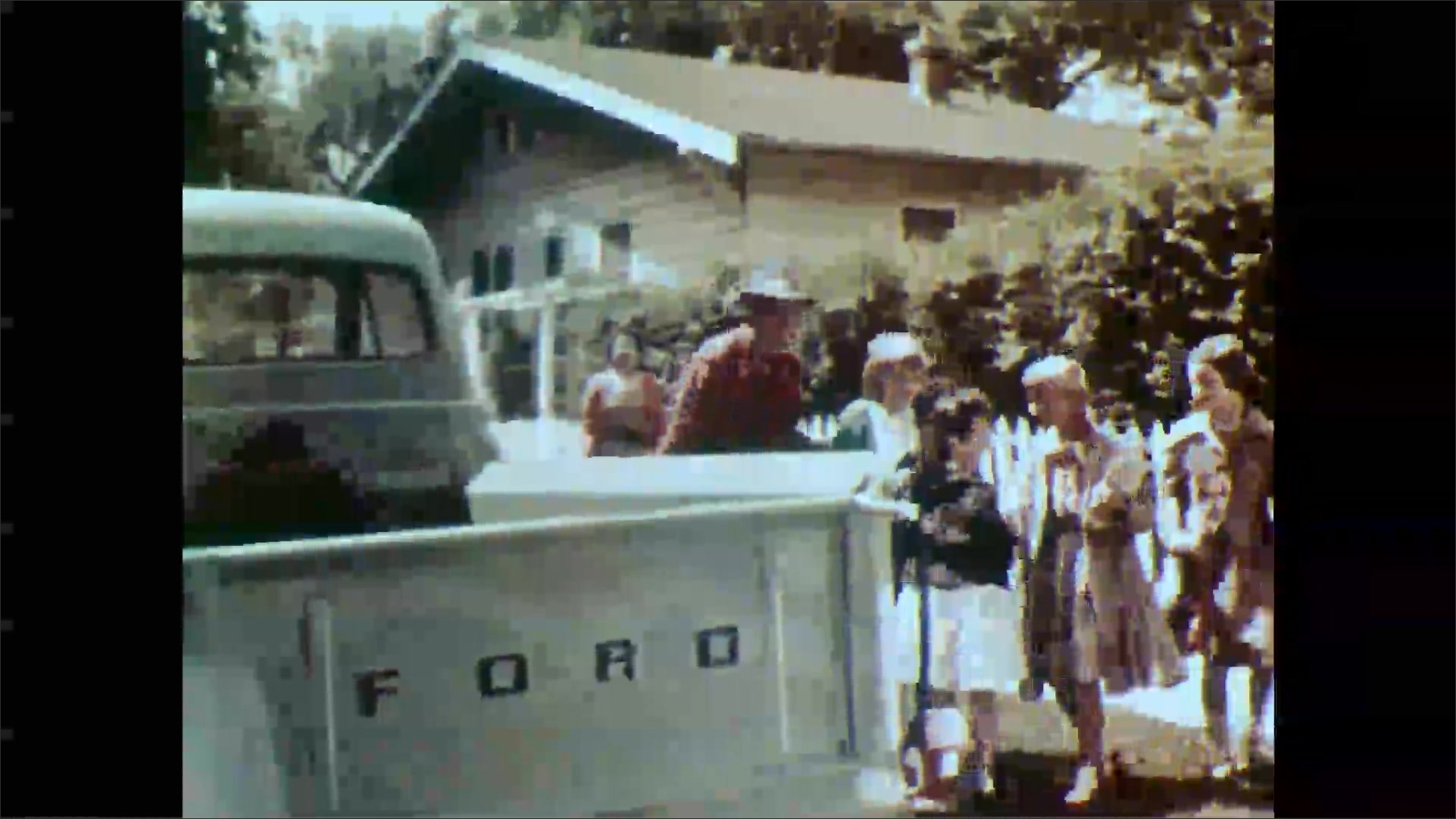 1950s: Girl runs toward and speaks to man and woman near fence. Man, woman and children walk towards truck. Man opens back of truck and retrieves black lamb. Girl looks into back of truck.