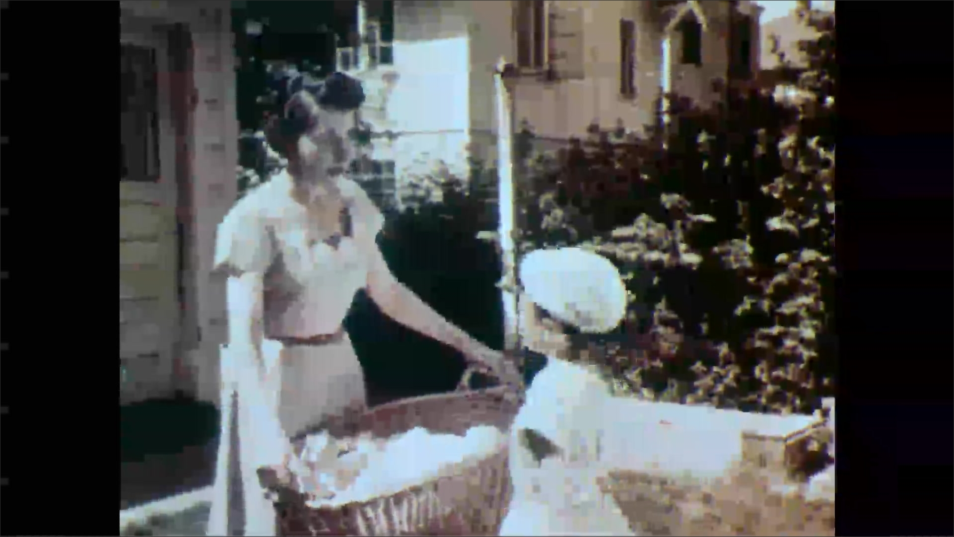1950s: Girl panics and looks around. Girl runs to open gate and then back to house. Woman carrying laundry talks to girl. Girl runs from woman with laundry basket.
