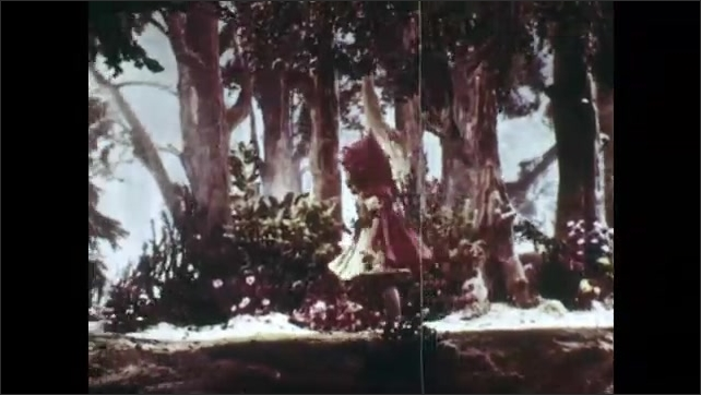 1940s: Animation of Little Red Riding Hood, she walks in the forest and looks around. Little Red Riding Hood walks in the forest, stops in the middle of her path and looks to her left.