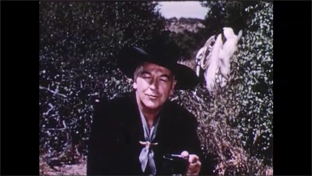 1950s: Man sits on log, pours coffee, waves, talks. Horse grazes on bush.