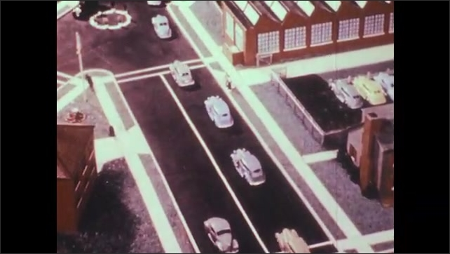 1940s: Two model cars drive around bend, third car passes in between sending them both off road. Cars drive single file down busy road.