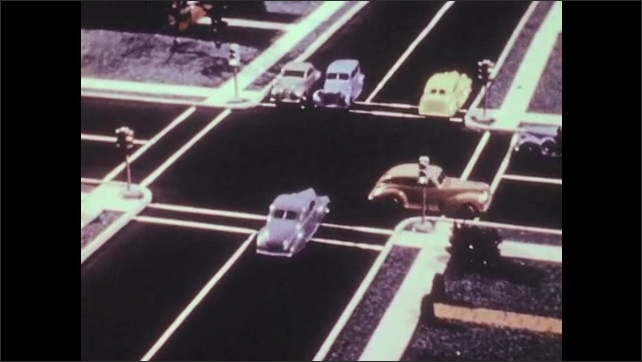 1940s: Model cars drive through four-way intersection. Car cuts off other car. Cars continue driving through intersection.