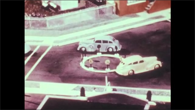 1940s: Model cars drive down road. Cars drive through intersection. Cars drive around round-about. Cars drive down two-way, three lane roads.