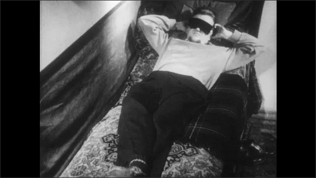 1950s: A chicken wears special glasses and moves its head. Man lays on sofa, removes sleep mask and puts special glasses, hits his head on the wall, touches the wall and stands up.