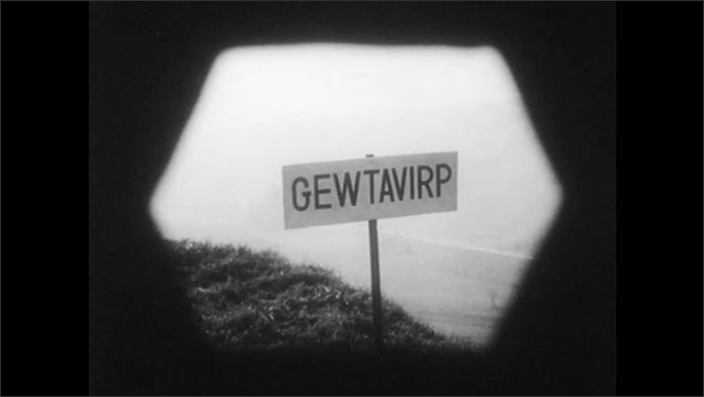"""1950s: View of field with sign that says """"Gewtavirp"""". Man wears special glasses, walks and touches the table and blackboard in lecture hall, students sit and observe."""