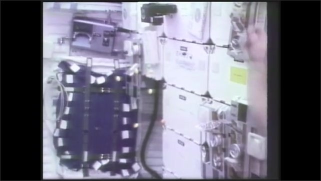 1990s:  Candy floats in midair. Astronaut plucks pieces of candy out of midair and eats it. Astronaut catches candy in his mouth.
