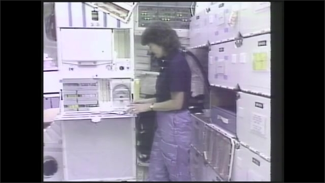 1990s: Sally Ride speaks while holding packages of food. Sally Ride inserts package of orange drink into water dispenser.