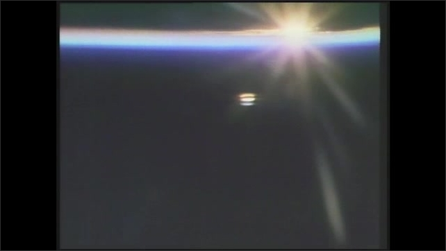 1990s: View of sunrise from space shuttle. Astronaut wearing sleep mask.