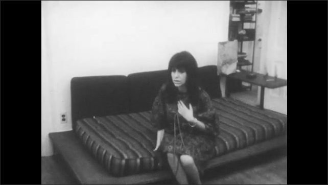 1960s: woman in dress talks to stereo cabinet speaker, gestures with  arms, sits on daybed, sings, talks and  listens in living room. woman walks between trees in park near cars on road.