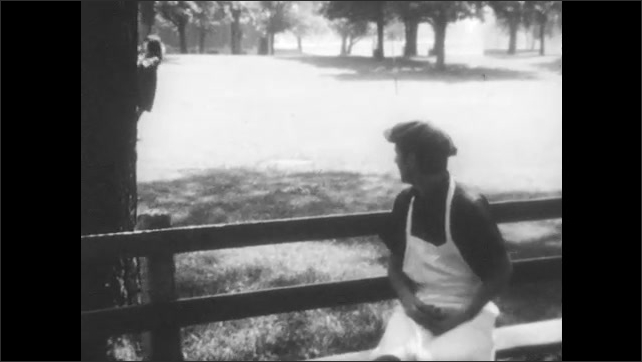 1960s: man in apron and cap walks back and forth, sits on bench and watches girl in dress run around holding string for a balloon in city park.