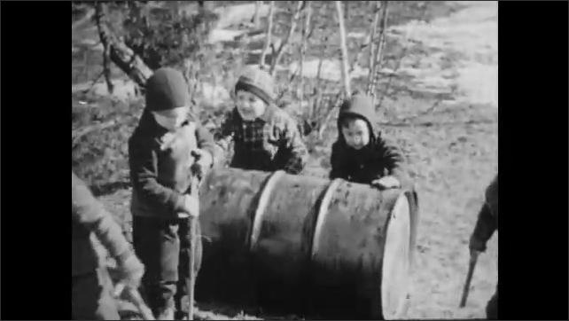 1950s: Boys roll barrel up a hill.
