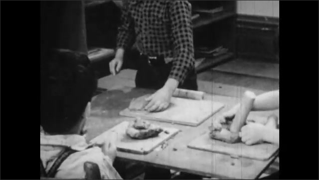 1950s: Group of children sit at table and play with clay. Kids throw clay, boys fight.