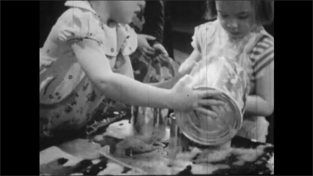 1950s: Girl pours liquid into various containers on table. Girl scoops liquid from containers. Girl blows through straw, makes bubbles on table.