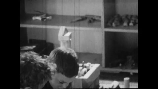 1950s: Boys playing, pull toy train. Boys playing around tower of blocks. Pan of tower, boys playing.