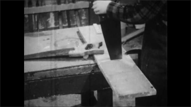 1950s: Boy sawing through board. Boy hits board with hammer.