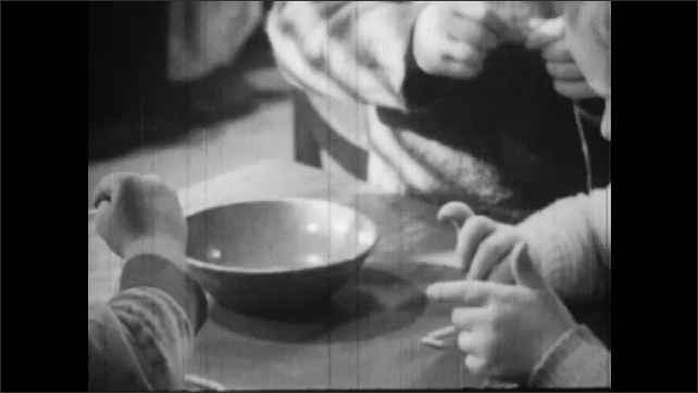 1950s: Close up, kids at table, stringing pasta on cords.