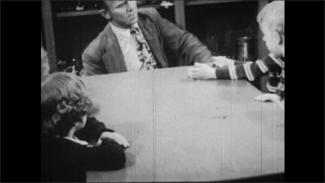 1950s: UNITED STATES: lady and girl watch cow being milked. Man milks cow. Man talks with children. Children sit at desk. Boy holds hamster.