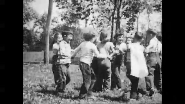 1950s: UNITED STATES: children play outside. Children dance in circle. Children holds hands in circle.