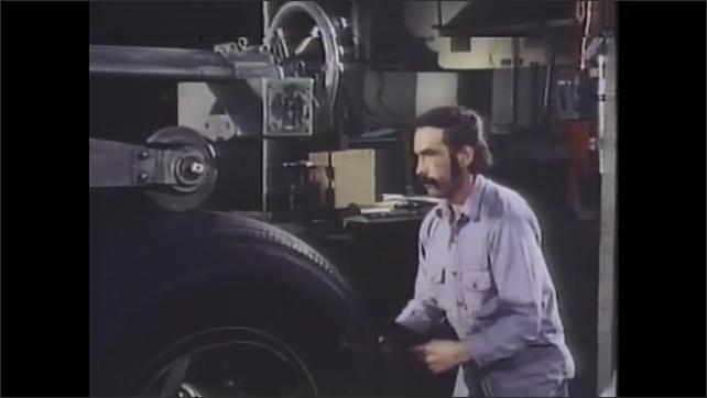 1980s: Man works on machine with large spinning wheel. Man works on airplane tire. Man spins tire on machine while checking calibrations.