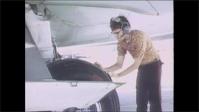 1980s: Man on airport runway signals to jetliner taxiing in to stop. Man takes measurements of jetliner wheel. Man works on wheel of jetliner in hangar while plane fuselage in behind him.