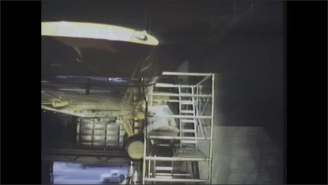 1980s: Man positioned in scaffolding around airplane, while working on it. Smoke is blown into hangar and test plane taxis through it, creating jet streams. Machine measures disbursed smoke.