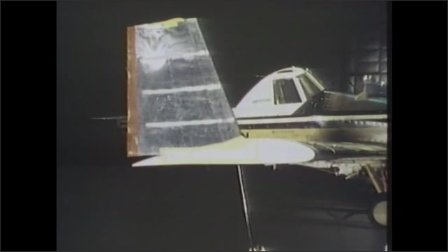 1980s: Bi-plane dusts field of crops. Model plane in wind tunnel. Bi-plane dusts field of crops.