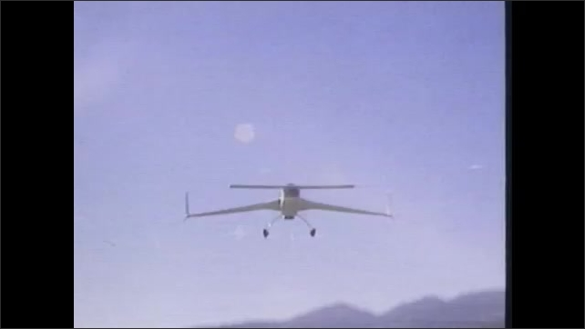 1980s: Small, personal plane takes off from runway at airport. Man with movie camera films plane flying over airfield. Airplane lands then taxis down runway.