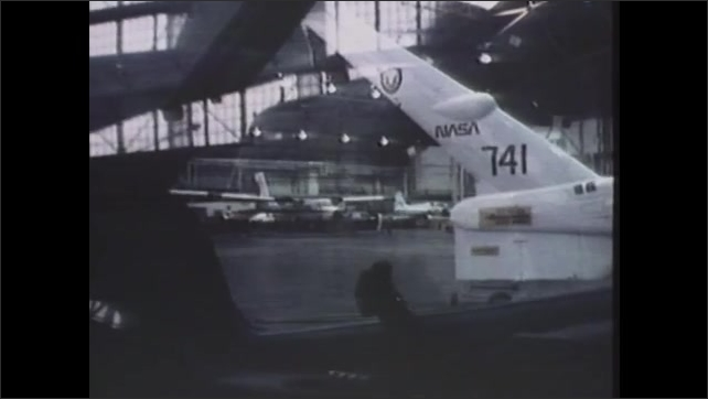 1980s: Airplane does a turn in the air. Hangar with airplanes and equipment. Chuck Jackson speaks while standing in front of plane and computer.