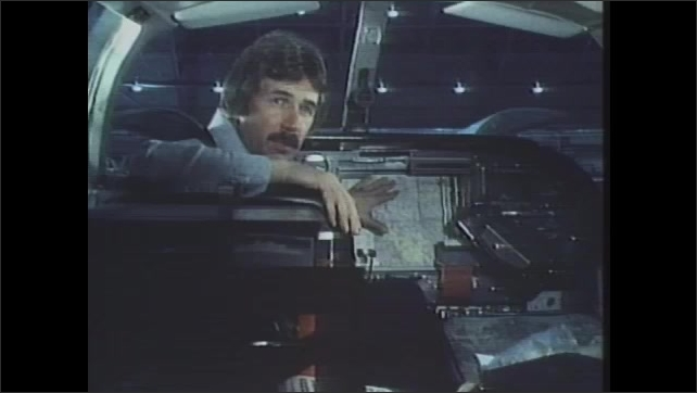 1980s: Machine draws on map. Man sits in cockpit of airplane, talking and pointing to map.