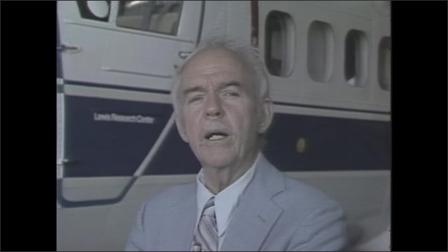 1980s: Man in suit stands next to airplane, talking. Title card: Nasa, The X-15 1960-1980.