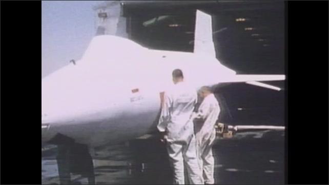 1980s: Jet plane flies through air. Man paint airplane. Men work on detailing painted plane. Jet flies through air.