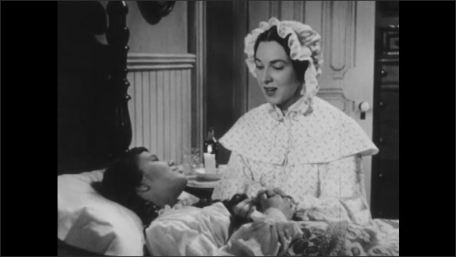 1950s: UNITED STATES: girl tells story to sister at night in bed. Girl sick in bed.
