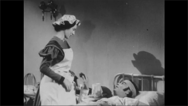 1950s: UNITED STATES: nurse tends to patient in military hospital. Lady talks to man. Man talks to lady.