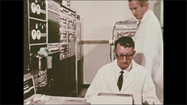 1960s: Packet of material is lowered into machine. Men in lab coats look at equipment. Graph flashes on screen. Valve doors.