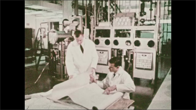 1960s: Men in lab coats look at papers. Man walks down stairs.