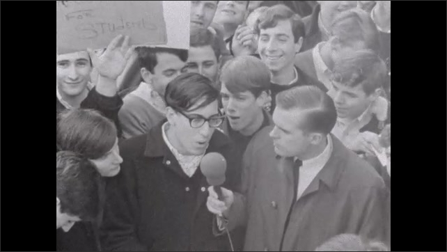 1950s: UNITED STATES: man interviews member of crowd in street. Student protest.