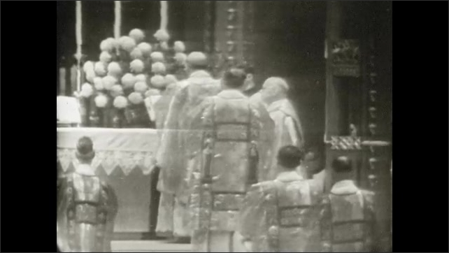 1950s: UNITED STATES: men at altar. Blessing of Virgin Mary. Flowers on altar. Choir chants. Dedication mass.