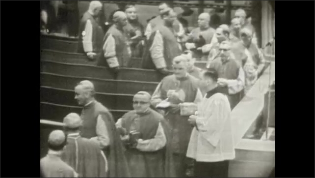 1950s: UNITED STATES: Bishop  in aisle of church. Baltimore Bishop. Men tip hats in aisle. Master of Ceremonies.